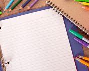 Scattered school supplies like pens, pencils, notebook